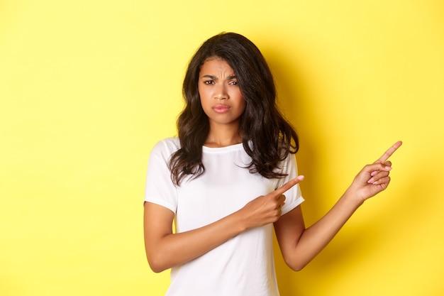 Porträt eines skeptischen und unlustigen afroamerikanischen mädchens, das etwas schlechtes beurteilt und mit den fingern richtig zeigt