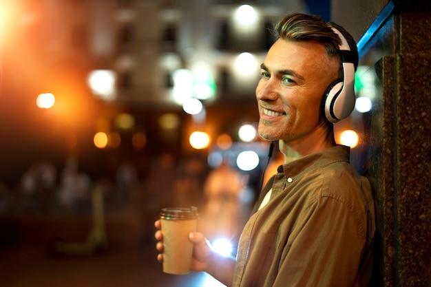 Porträt eines smiley-mannes in der stadt nachts mit kopfhörern und kaffeetasse