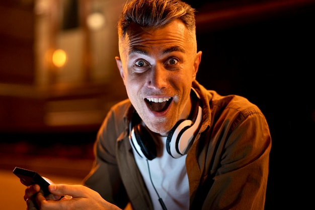 Porträt eines smiley-mannes in der stadt nachts mit kopfhörern und smartphone
