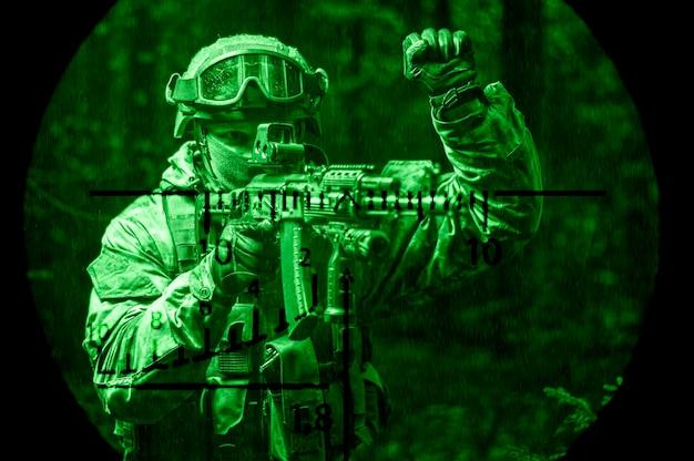 Porträt eines soldaten, der durch den wald geht. er hob die hand, um seinen partner vor der gefahr zu warnen. blick durch ein optisches visier. nachtsichtgerät. grünes licht
