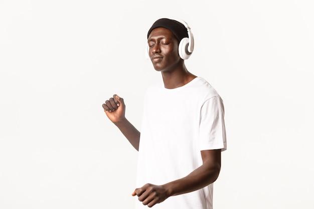 Porträt eines sorglosen attraktiven afroamerikaners, der die augen schließt und tanzt, während er musik in drahtlosen kopfhörern hört