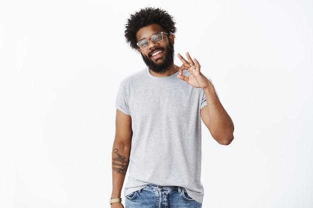 Porträt eines sorglosen selbstbewussten und versicherten gutaussehenden afroamerikanischen bärtigen mannes mit brille, der eine ok geste zeigt, um den plan perfekt zu bestätigen, zuzustimmen und eine positive meinung abzugeben
