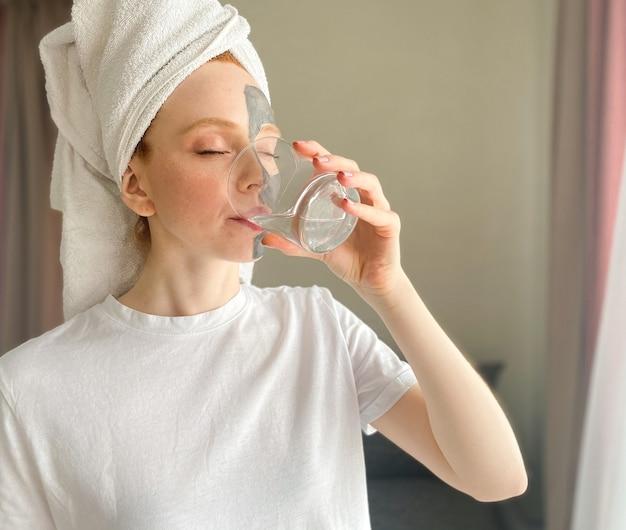 Porträt eines spa-mädchens in hauskleidung mit einem handtuch auf dem kopf und einer maske im gesicht, die ein sauberes glas wasser trinkt