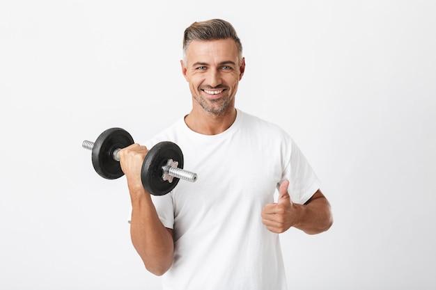 Porträt eines sportlers der 30er jahre mit borsten, der ein lässiges t-shirt trägt, das bizeps pumpt und die hantel einzeln auf weiß hebt