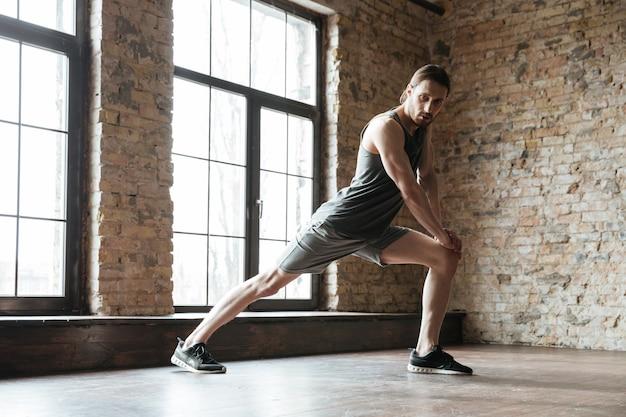 Porträt eines sportlers, der sich im fitnessstudio aufwärmt