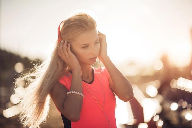Porträt eines sportlichen jugendlichen mädchens, das vom trainieren ruht, musik mit kopfhörern hörend, draußen lächelnd verwendet. fitness und sport lifestyle, sonnige fackel außen.