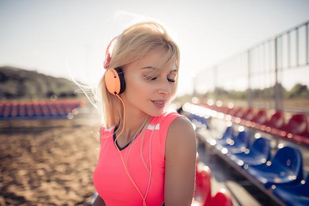 Porträt eines sportlichen jugendlichen mädchens, das vom trainieren ruht, musik mit kopfhörern hört und draußen lächelt.