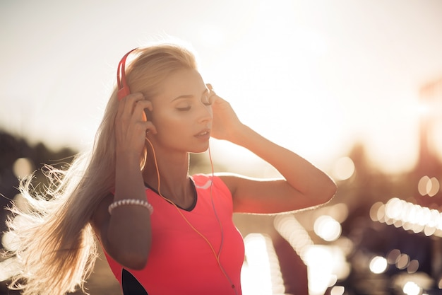 Porträt eines sportlichen jugendlichen mädchens, das vom training ruht, musik mit kopfhörern hörend, draußen lächelnd verwendet. fitness- und sportlebensstil, sonniges äußeres.