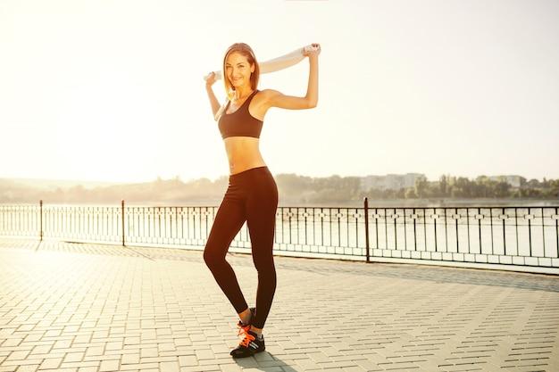 Porträt eines sportlichen mädchens. schönes junges sporteignungsmodell, das zum rütteln im stadtpark fertig wird.