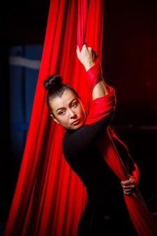 Porträt eines sportmädchens auf einem hintergrund von roten tüchern für luftgymnastik. studioaufnahmen auf dunklem hintergrund,