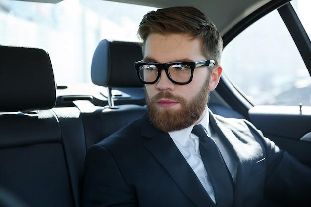Porträt eines srious jungen mannes, der anzug und brille trägt