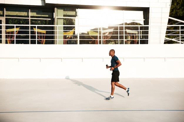 Porträt eines starken afrikanischen sportlers in den kopfhörern in voller länge