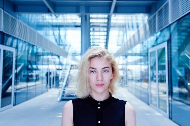 Porträt eines starken blonden mädchens im schwarzen von der zukunft vor dem hintergrund eines glasgeschäftsgebäudes, welches die kamera betrachtet