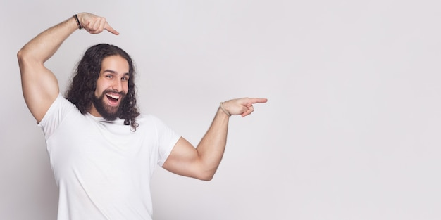 Porträt eines starken bodybuilders im weißen t-shirt mit langem, gewelltem haar und bart, stehend, mit zahnigem lächeln in die kamera schauen und auf hellgrauen hintergrundkopierraum zeigend. innenstudio erschossen.