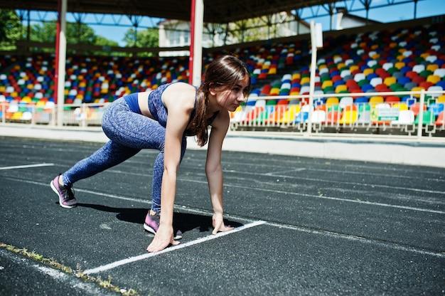 Porträt eines starken sitzmädchens in der sportkleidung, die in das stadion läuft.