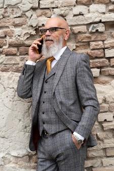 Porträt eines stilvollen älteren mannes auf seinem telefon his