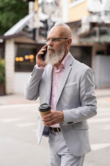 Porträt eines stilvollen älteren mannes, der am telefon spricht