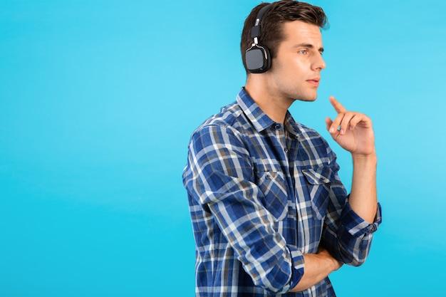 Porträt eines stilvollen, attraktiven, gutaussehenden jungen mannes, der musik über drahtlose kopfhörer hört und spaß im modernen stil hat, glückliche emotionale stimmung