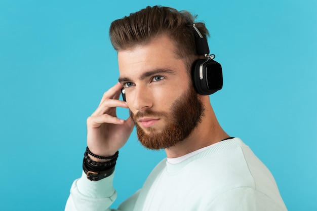 Porträt eines stilvollen, attraktiven jungen bärtigen mannes, der musik über drahtlose kopfhörer hört, moderne, selbstbewusste stimmung