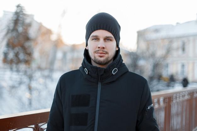 Porträt eines stilvollen attraktiven jungen mannes mit einem bart in einer stilvollen schwarzen winterjacke in einer strickmütze an einem warmen wintertag. brutaler modischer typ.