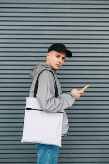 Porträt eines stilvollen jungen mannes in freizeitkleidung, der eine öko-tasche auf seinen schultern trägt und auf steht
