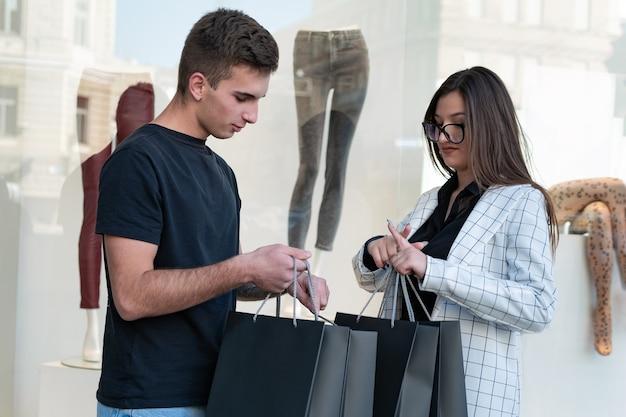 Porträt eines stilvollen jungen paares im einkaufszentrum mit einkäufen in ihren händen.