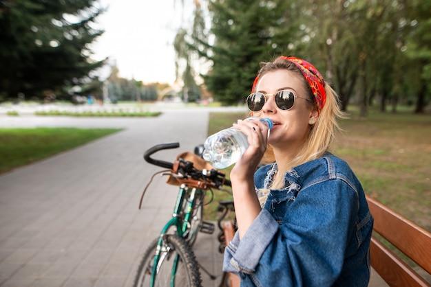Porträt eines stilvollen mädchens in der sozialen brille, die auf einer bank im park sitzt und wasser aus einer flasche ruht und trinkt