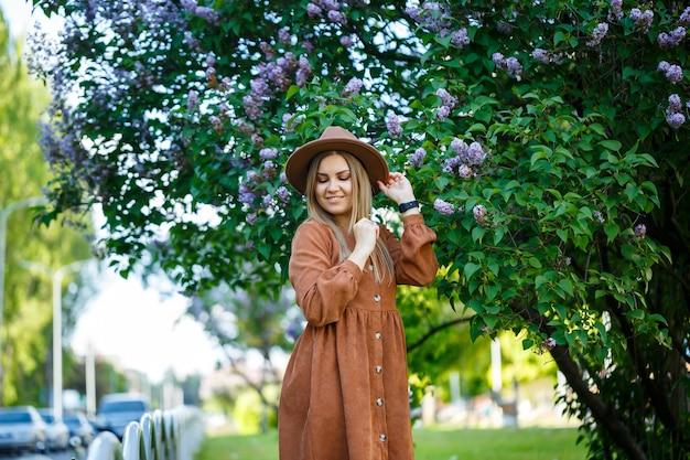 Porträt eines stilvollen mädchens in einem braunen hut und kleid auf einem hintergrund des fliederbaums an einem sonnigen warmen tag. eine junge frau von europäischem aussehen mit einem lächeln im gesicht