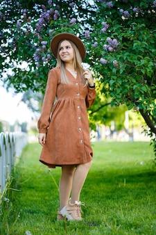 Porträt eines stilvollen mädchens in einem braunen hut und kleid auf einem lila hintergrund. junge frau von europäischem aussehen mit einem lächeln im gesicht