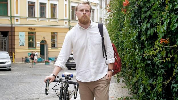 Porträt eines stilvollen männlichen hipsters mit retro-fahrrad auf der stadtstraße.