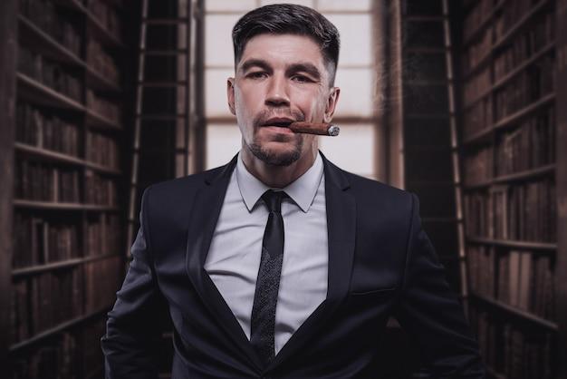 Porträt eines stilvollen mannes im anzug mit zigarre. geschäftskonzept. gemischte medien