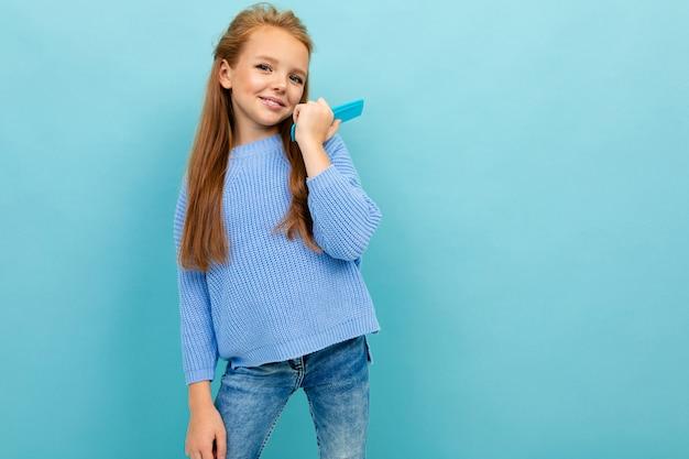 Porträt eines stilvollen schönen reizend schulmädchens in einer blauen strickjacke mit einer haarbürste auf einem hintergrund der blauen wand