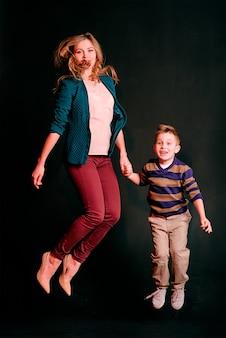 Porträt eines stilvollen süßen kleinen jungen mit schöner mutter, die im fotostudio springt