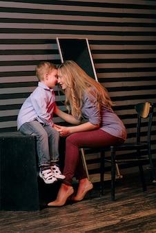 Porträt eines stilvollen süßen kleinen jungen mit schöner mutter im fotostudio