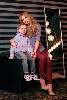 Porträt eines stilvollen süßen kleinen jungen mit umarmter schöner mutter im fotostudio
