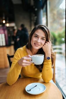 Porträt eines stilvollen trinkenden kaffees der jungen frau im café, kamera betrachtend.