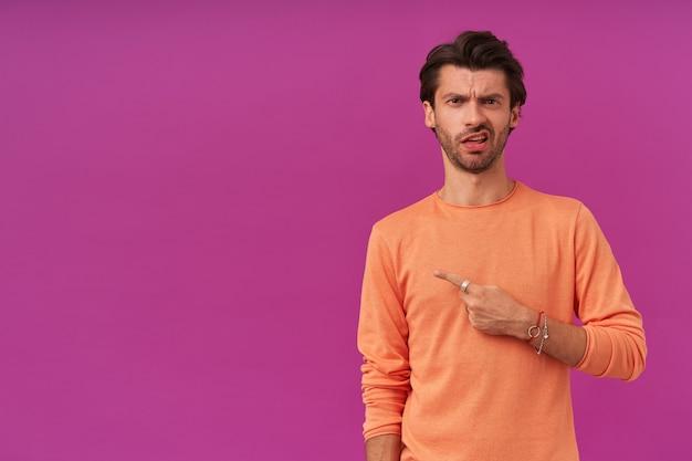 Porträt eines stirnrunzelnden, unzufriedenen mannes mit brünetten haaren und borsten. trage einen orangefarbenen pullover