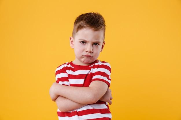 Porträt eines stirnrunzelnden verärgerten kleinen jungen, der kamera betrachtet