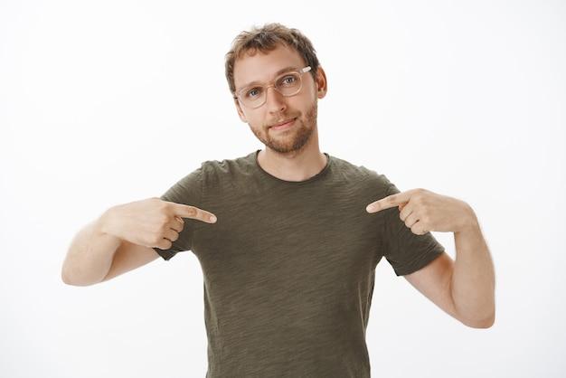 Porträt eines stolzen und erfreuten selbstbewussten gutaussehenden männlichen unternehmers in brille und dunkelgrünem t-shirt, der auf sich selbst zeigt und mit eigenen errungenschaften prahlt