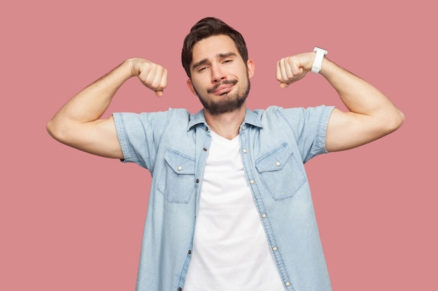 Porträt eines stolzen, zufriedenen, gutaussehenden, bärtigen jungen mannes im blauen hemd im casual-stil, der in bodybuilding-pose steht und seine stärke zeigt. indoor-studioaufnahme, isoliert auf rosa hintergrund.