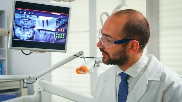 Porträt eines stomatologen, der älteren frau mit digitalem röntgen im hintergrund die behandlung erzählt. arzt, der in einem modernen stomatologischen büro arbeitet und die röntgenaufnahme der zähne vom digitalen monitor erklärt