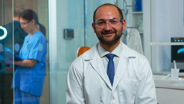 Porträt eines stomatologen, der in der zahnarztpraxis in die kamera lächelt, während die krankenschwester mit dem patienten im hintergrund spricht. zahnmediziner, der auf der webcam auf dem stuhl in der stomatologischen klinik sitzt.