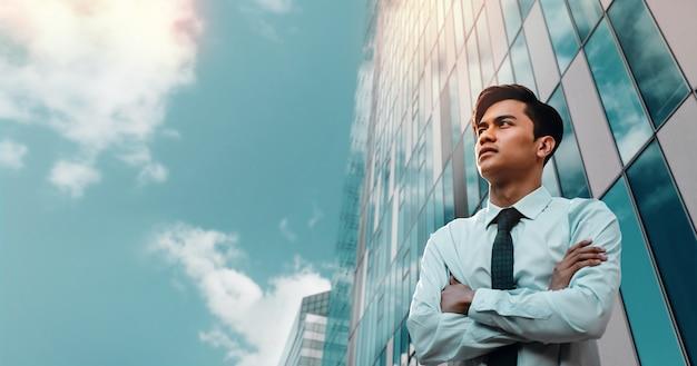 Porträt eines strebenden jungen asiatischen geschäftsmannes in der stadt. verschränkte arme und blick in den himmel.
