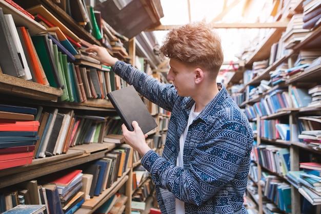 Porträt eines studenten, der bücher aus öffentlichen bibliotheksregalen durchsucht.