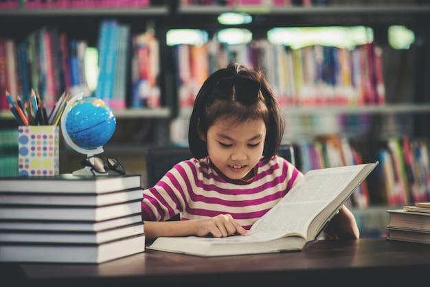 Porträt eines studentenkindermädchens, das an der bibliothek studiert