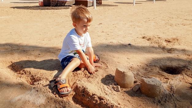 Porträt eines süßen 3-jährigen kleinkindjungen, der am sandstrand sitzt und mit spielzeug spielt und sandburg baut