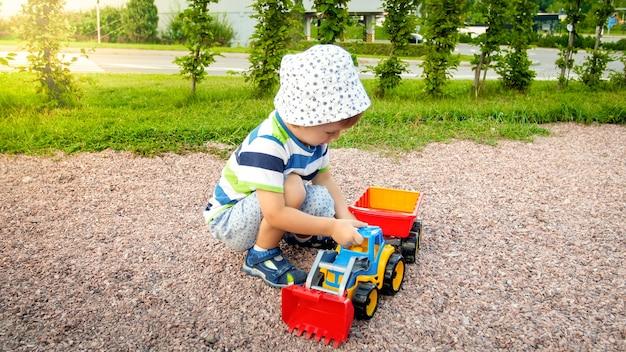 Porträt eines süßen 3-jährigen kleinkindjungen, der auf dem spielplatz im park sitzt und mit buntem plastikspielzeug-lkw spielt. kinder, die spaß haben und mit spielzeug im freien spielen