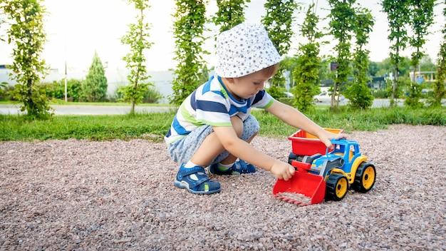Porträt eines süßen 3-jährigen kleinkindjungen, der auf dem spielplatz im park sitzt und mit buntem plastikspielzeug-lkw spielt
