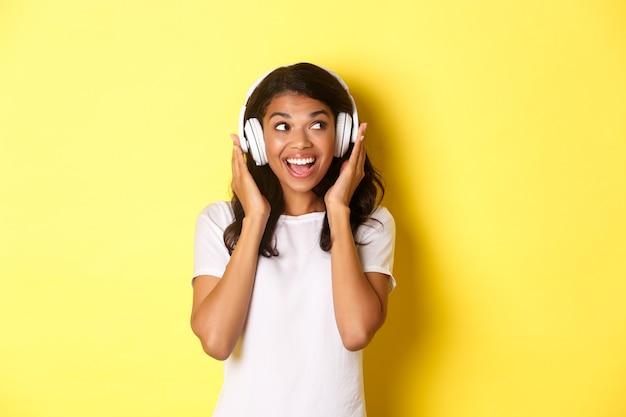 Porträt eines süßen afroamerikanischen mädchens, das lächelt, während es musik in kopfhörern hört und beiseite schaut