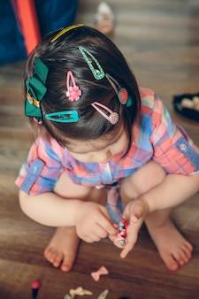 Porträt eines süßen babykopfes mit vielen haarspangen, die zu hause über einem holzboden spielen. selektiver fokus auf den kopf.